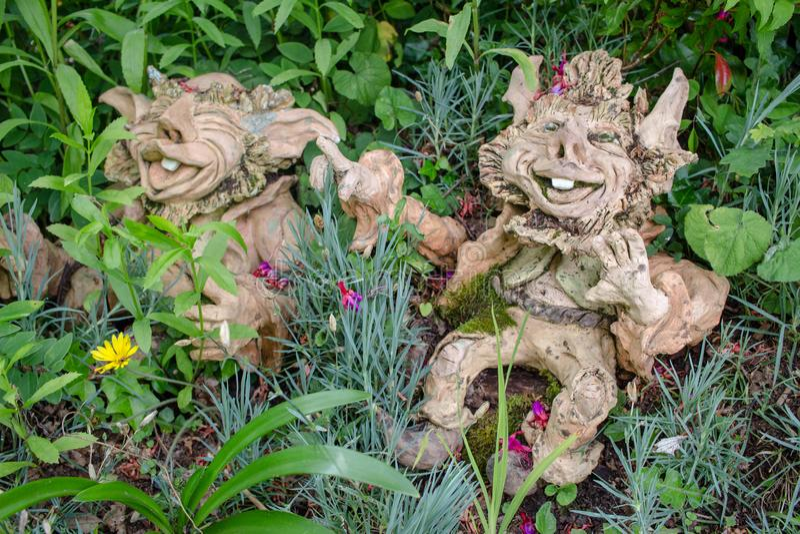 Gnomos del jardín con las sonrisas traviesas que se sientan en flores e hierba i imagenes de archivo