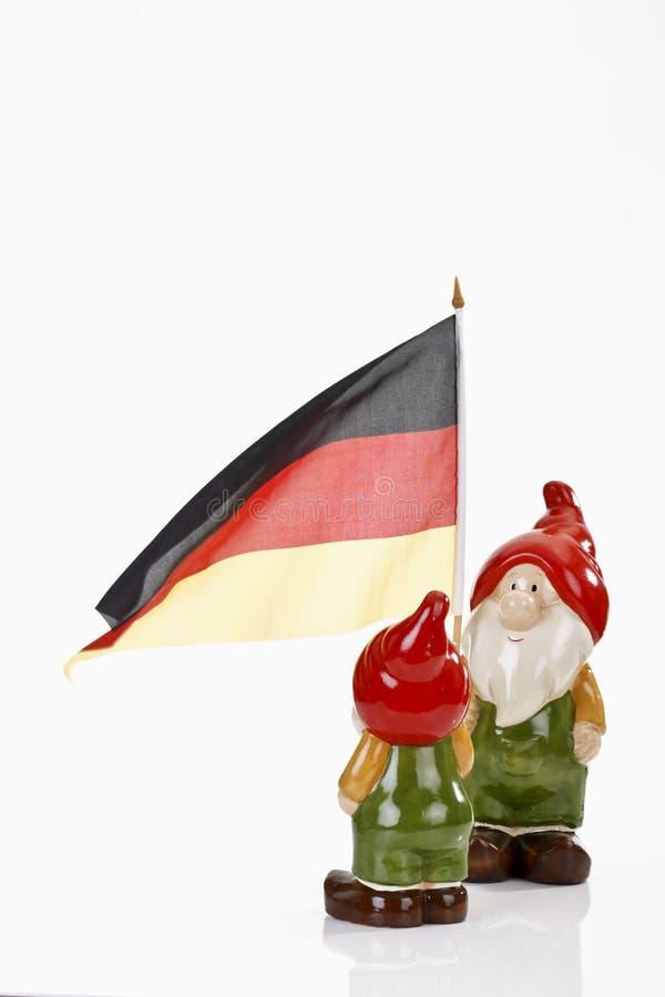 Gnomos del jardín y bandera alemana en el fondo blanco foto de archivo