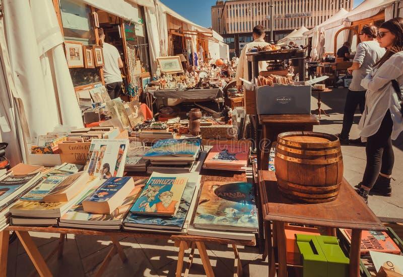 Goście patrzeje stare książki przy pchli targ plenerowym z retro zabawkami, naczynia, drugi ręki personel obraz stock