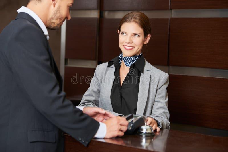 Gość płaci hotelowego rachunek z kredytową kartą zdjęcie royalty free