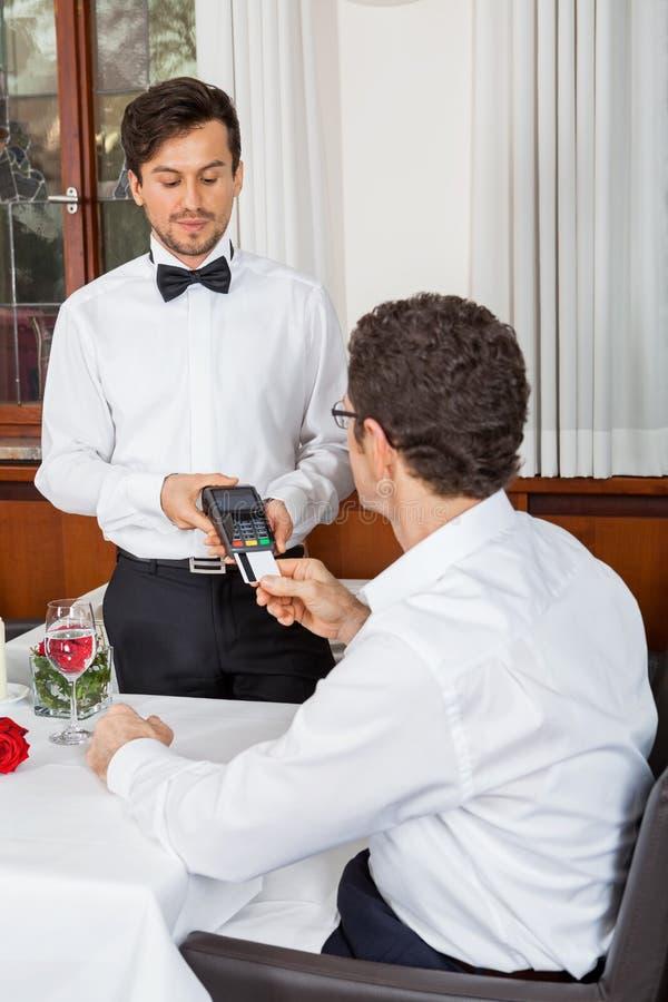 Gość restauracji w restauracyjnym mężczyzna i kobieta płacimy kredytową kartą zdjęcie royalty free