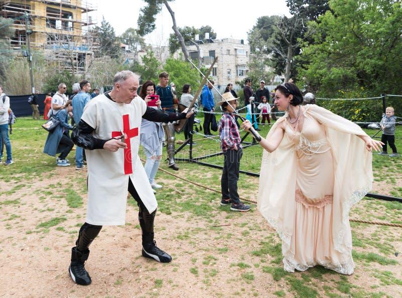 Gość ubierał w krzyżowa kostiumu i gość ubierał w kostiumach princesses walczą z kordzikami przy Purim festiwalem z fotografia royalty free
