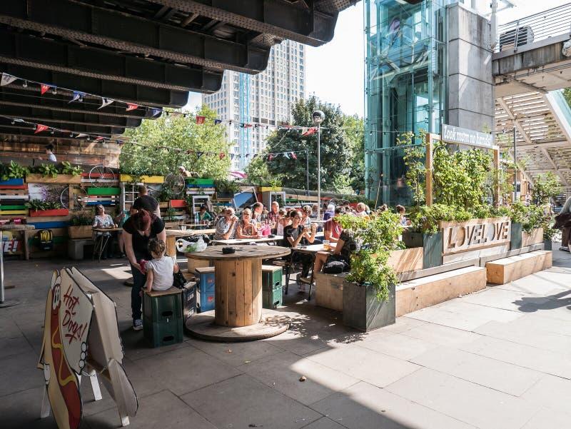 Goście restauracji relaksują w Sierpniowym słońcu przy plenerową kawiarnią na Londyn południe zakazie zdjęcie stock