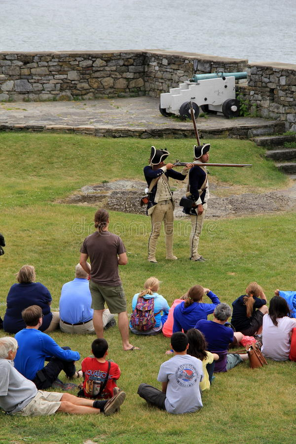 Goście siedzi lub stoi blisko młodych człowieków ponownych - odgrywać ostrzał muszkiety, fort Ticonderoga, Nowy Jork, 2014 obrazy royalty free
