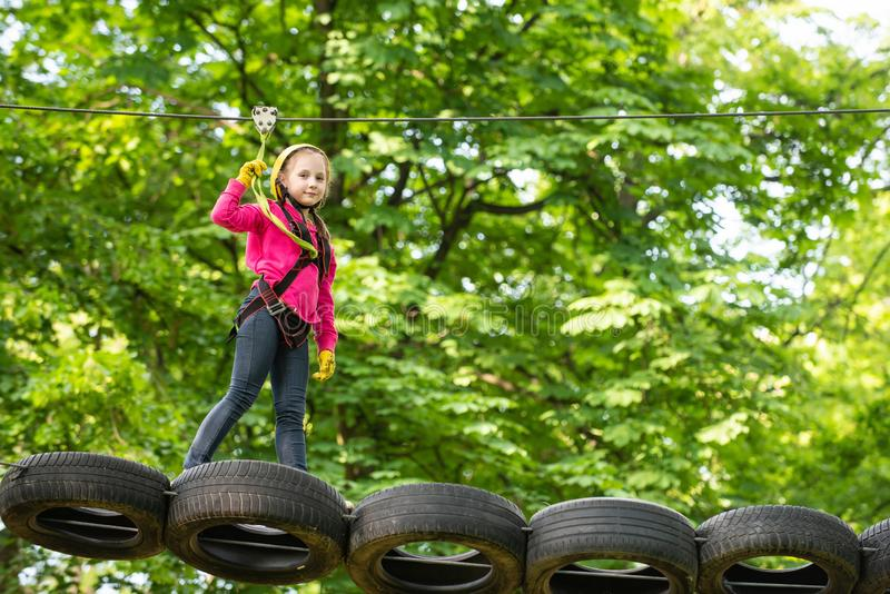Go Ape Adventure. Toddler climbing in a rope playground structure. Cute child in climbing safety equipment in a tree. House or in a rope park climbs the rope stock photography