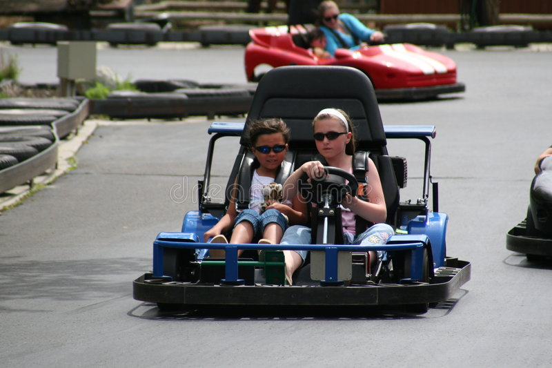 Go carts. Girls racing go carts on a sunny day royalty free stock photography