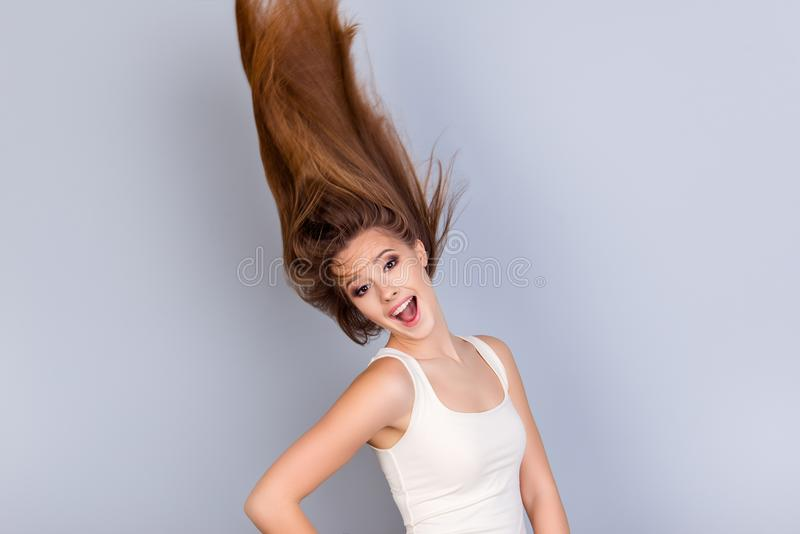 Go crazy and dream big! Dreamy charmed young blond lady in casual outfit is is so happy and funky, her hair is flying in. The air, she stands on a pure grey royalty free stock image