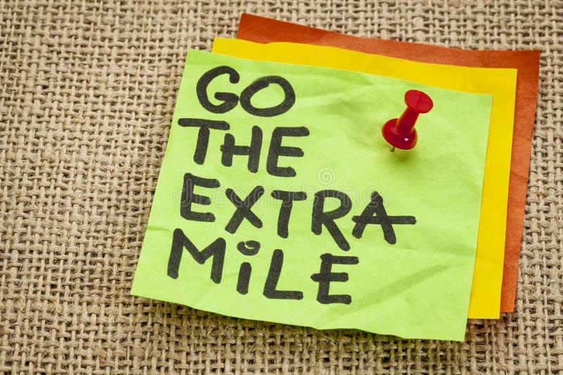 Go the extra mile reminder. Go the extra mile - motivational reminder - handwriting on sticky note royalty free stock photography