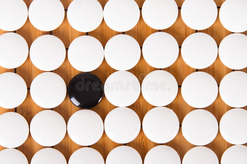Go Game. Black stone standing out from white pieces on Chinese go game board stock image