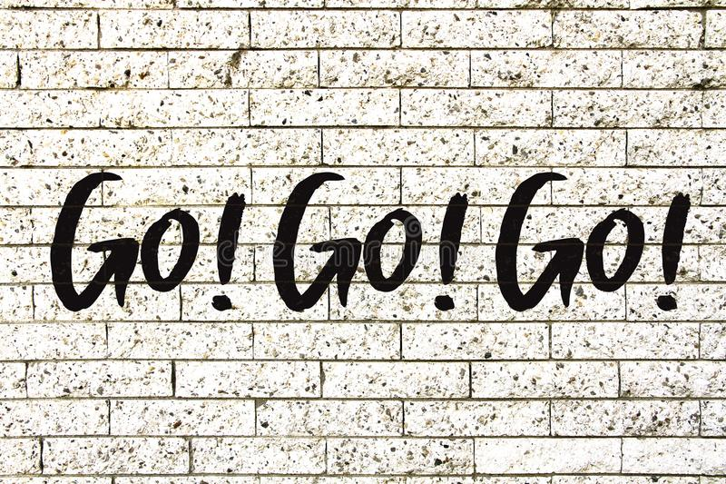 """""""Go! Go! Go!"""" motivational text written on a white stone brick wall background.  vector illustration"""