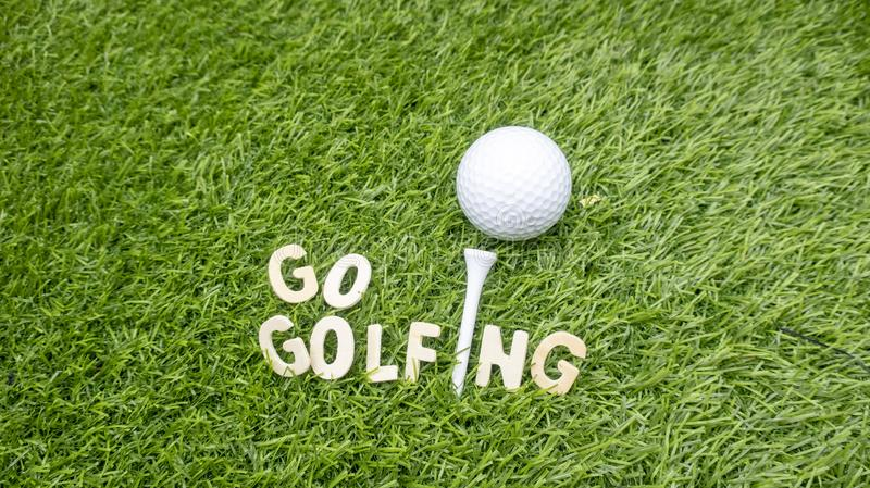 Go golfing with golf ball on green grass royalty free stock images