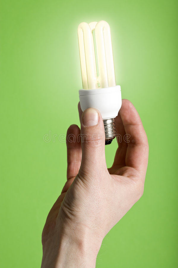 Go green. Hand holding shining energy saving lamp, green background stock image