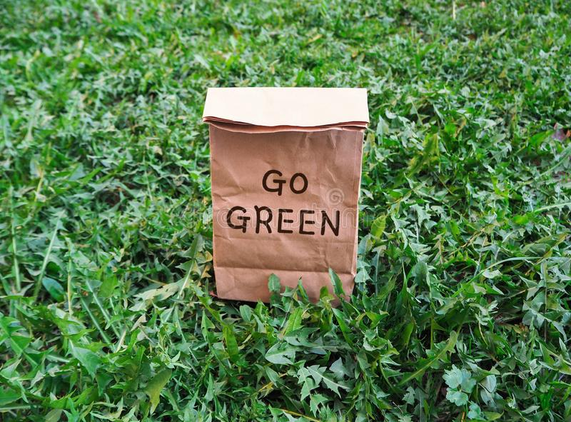 Go green ecological shopping bag on the green grass stock image