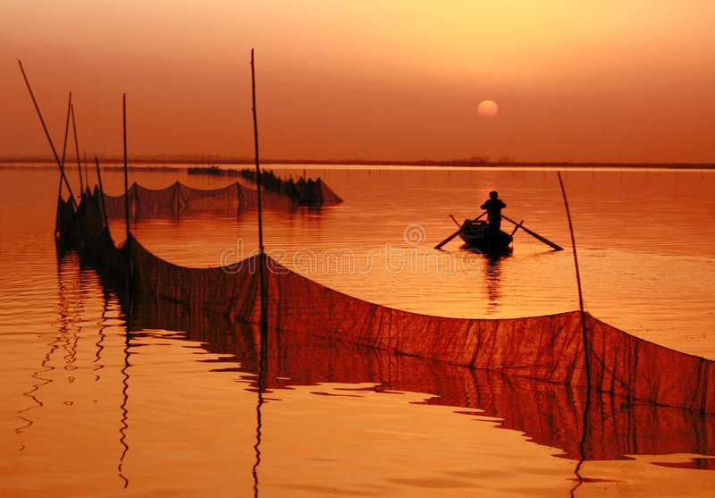 Go home. A fishman is going home at sunset royalty free stock images