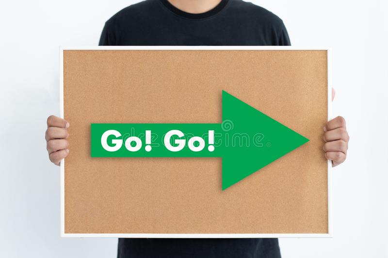 Go! Go!  man written text on broad arrow pointing to gold sign copy spaces stock images