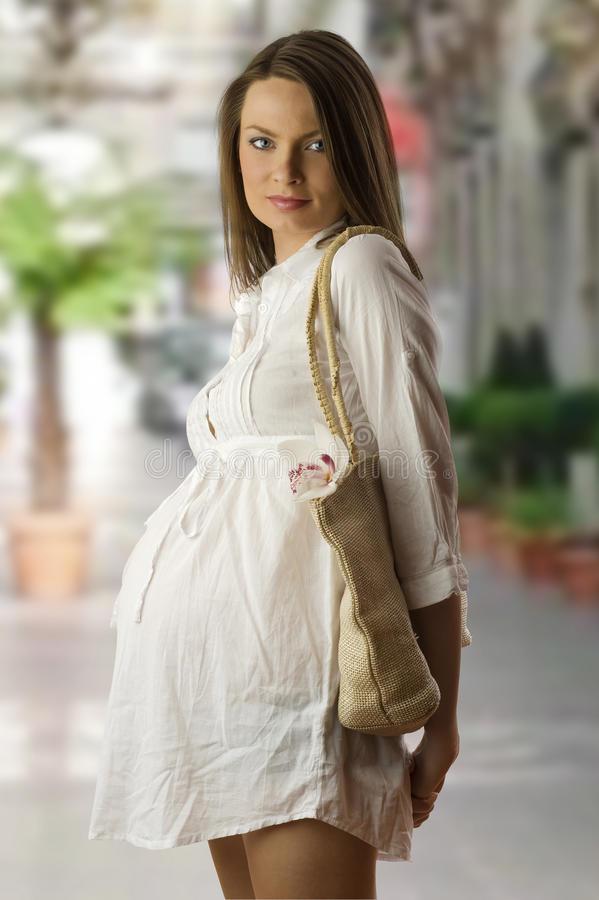 Go for shopping. Very nice pregnant woman in white prenatal dress with bag for shopping stock photography