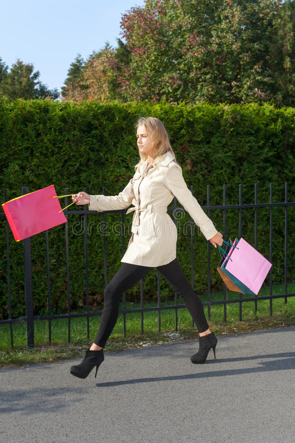 Go for shopping. Girl on high heels with full shopping bags stock photo