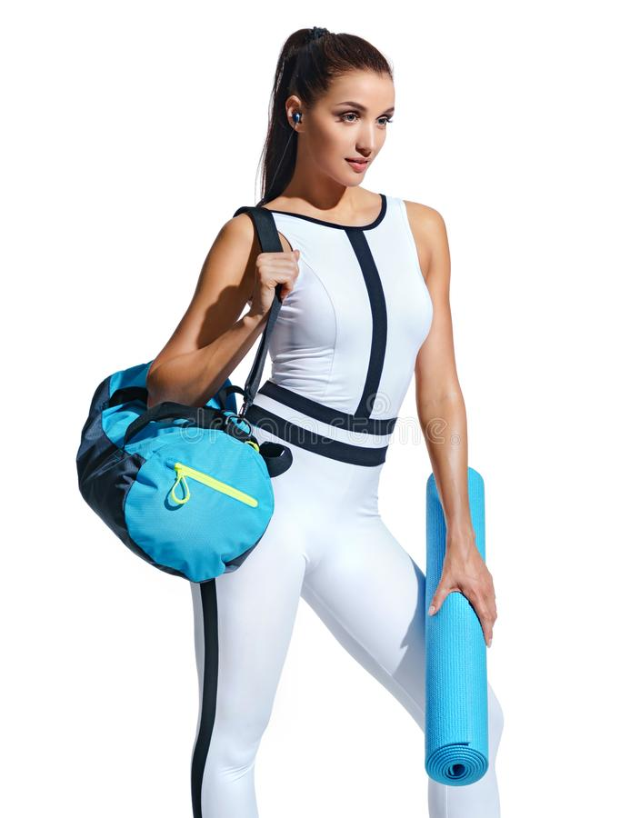 Attractive latin woman in fashionable sportswear with sports bag on white background. Go to gym! Attractive latin woman in fashionable sportswear with sports royalty free stock photos