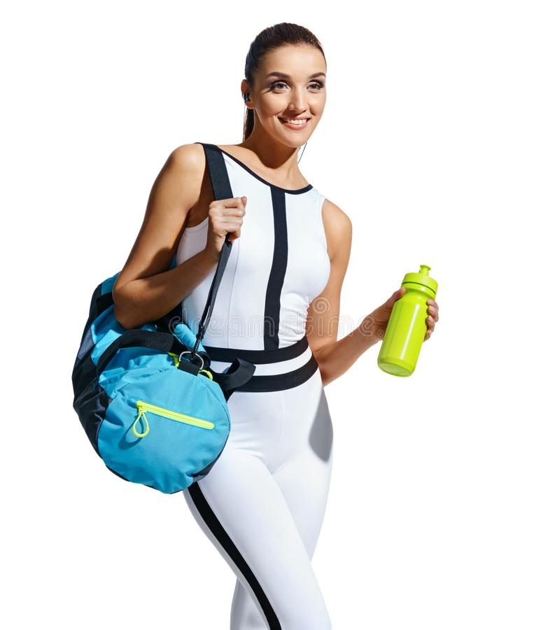 Smiling sporty woman in fashionable sportswear with sports bag and shaker on white background. Go to gym! Smiling sporty woman in fashionable sportswear with royalty free stock photo
