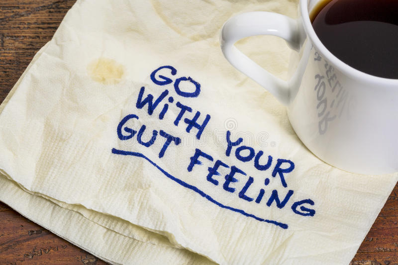 Go with your gut feeling. Advice or motivational reminder on a napkin with cup of espresso coffee royalty free stock photography