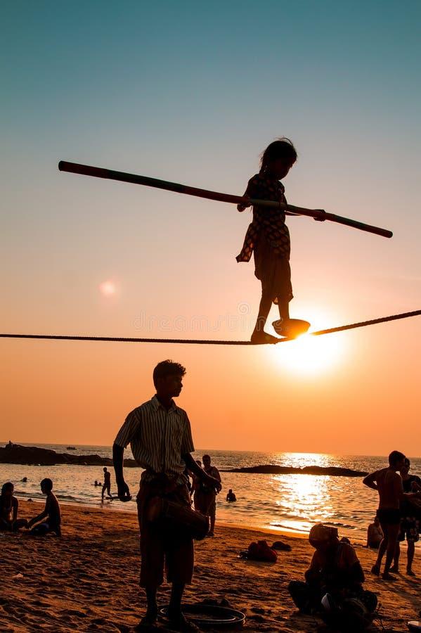 Goa, Índia - 4 de julho de 2017: menina nova do artista da rua durante a exposição na praia com por do sol bonito sobre o Oceano  fotografia de stock