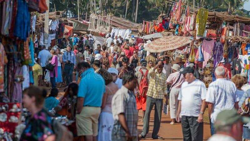 Goa, Índia - em janeiro de 2008 - turistas e comerciantes locais na feira da ladra semanal famosa em Anjuna imagem de stock royalty free