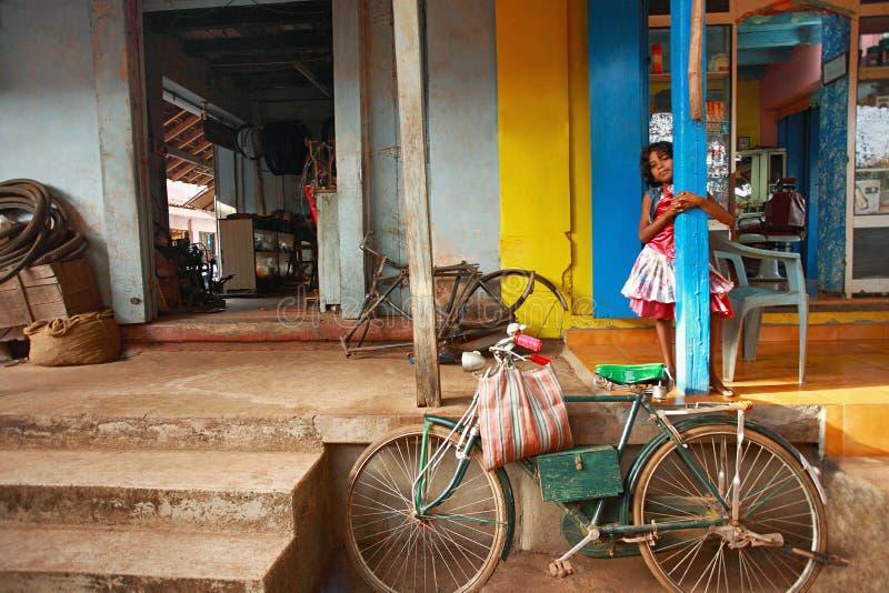 GOA, ÍNDIA, em maio de 2012, menina na oficina de reparações do ciclo no mercado Goa norte de Bicholim imagem de stock