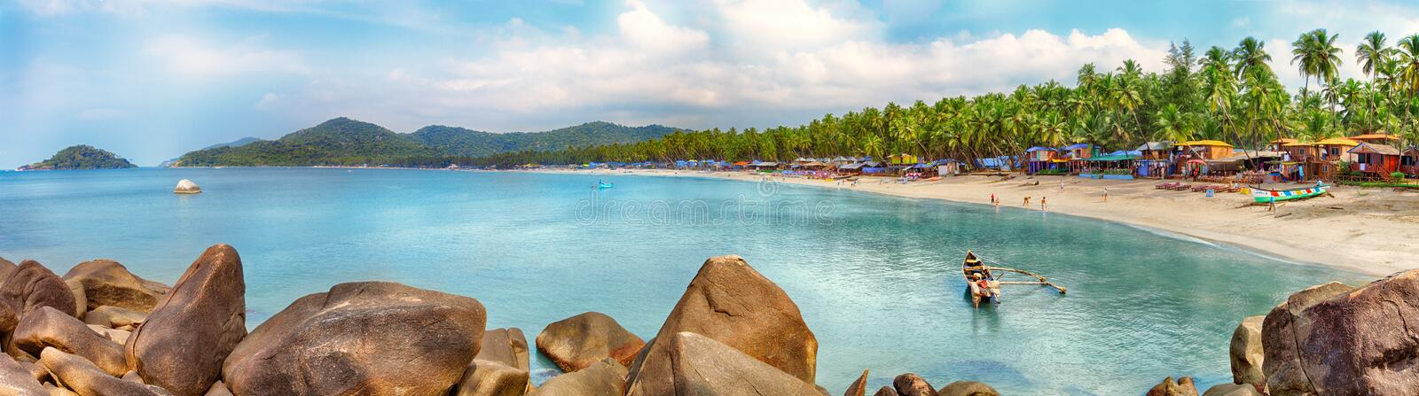 Goa beach panorama, Palolem, India. Beautiful Goa province beach in India with fishing boats and stones in the sea royalty free stock photos