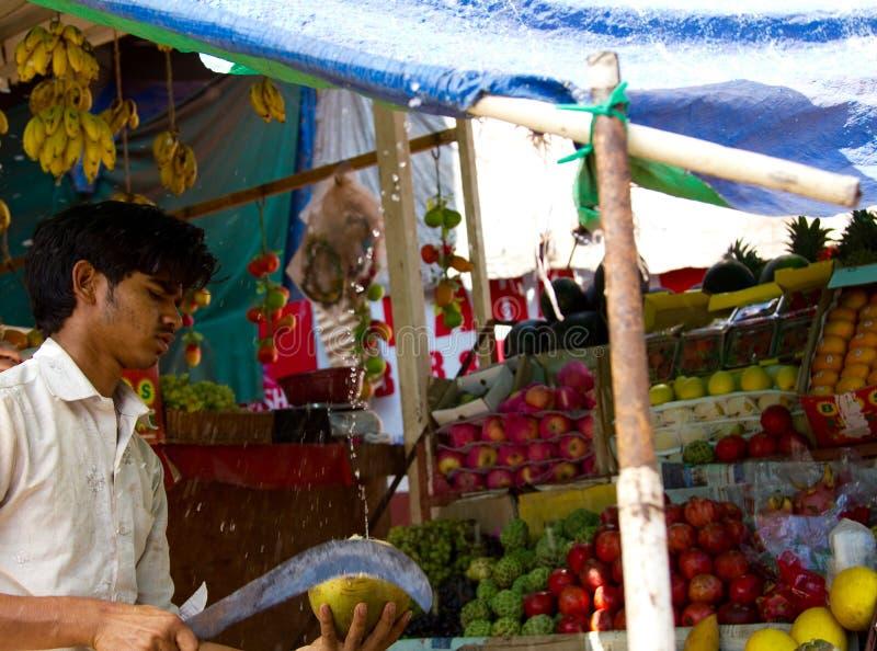 Goa, Inde - 16 décembre 2016 : Un vendeur de fruit de bord de la route prépare une noix de coco verte pour la consommation images libres de droits