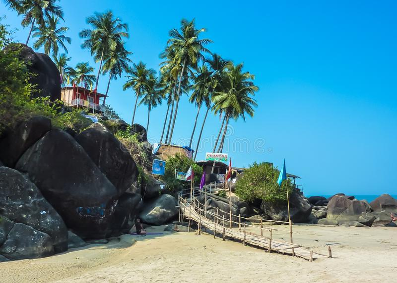 Bright traditional bungalow, standing on a high mountain, against the backdrop of palm trees and bright blue sky, Palolem beach royalty free stock photo