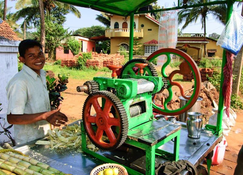 Goa, India - 16 novembre 2014: Giovane che cucina e che vende il succo popolare della canna della via del ` s dell'India fotografia stock