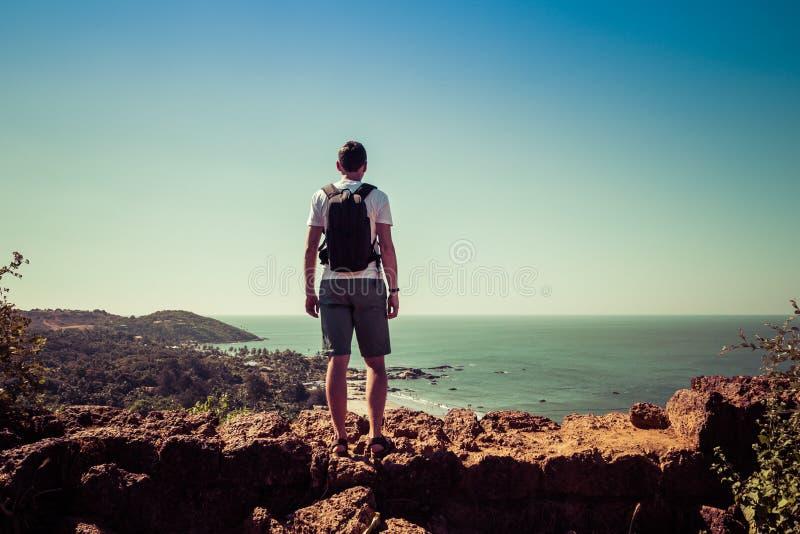 Goa, Indien - 20. Dezember 2018: Mann steht auf einer hohen Klippe, die den Strand Vagator betrachtet stockfoto
