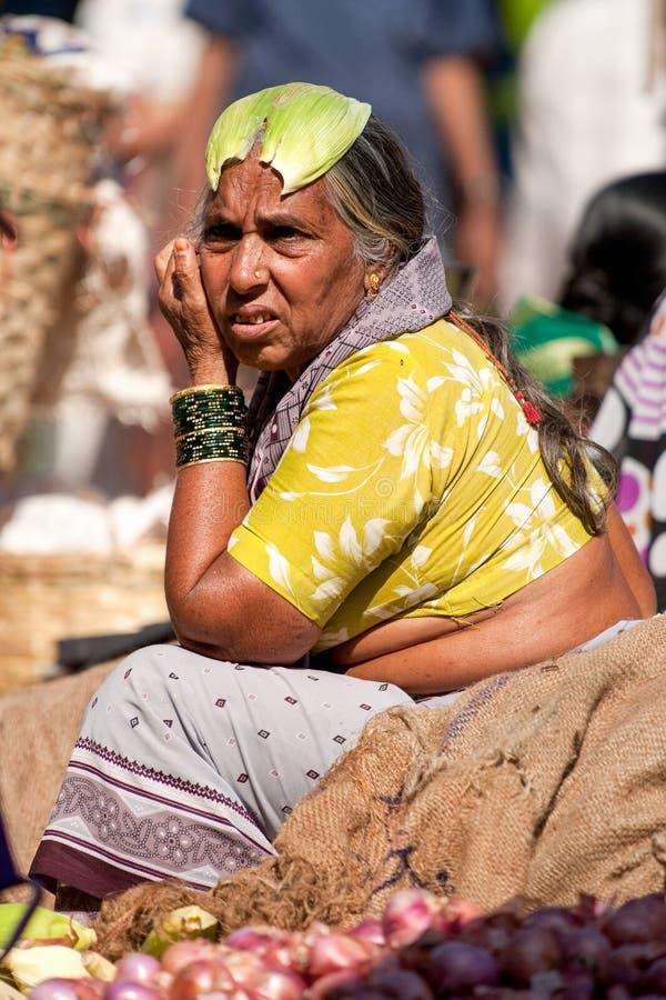 Goa Indien - Februari 2008 - kvinna som säljer nya grönsaker på den berömda veckoMapusa marknaden royaltyfri foto