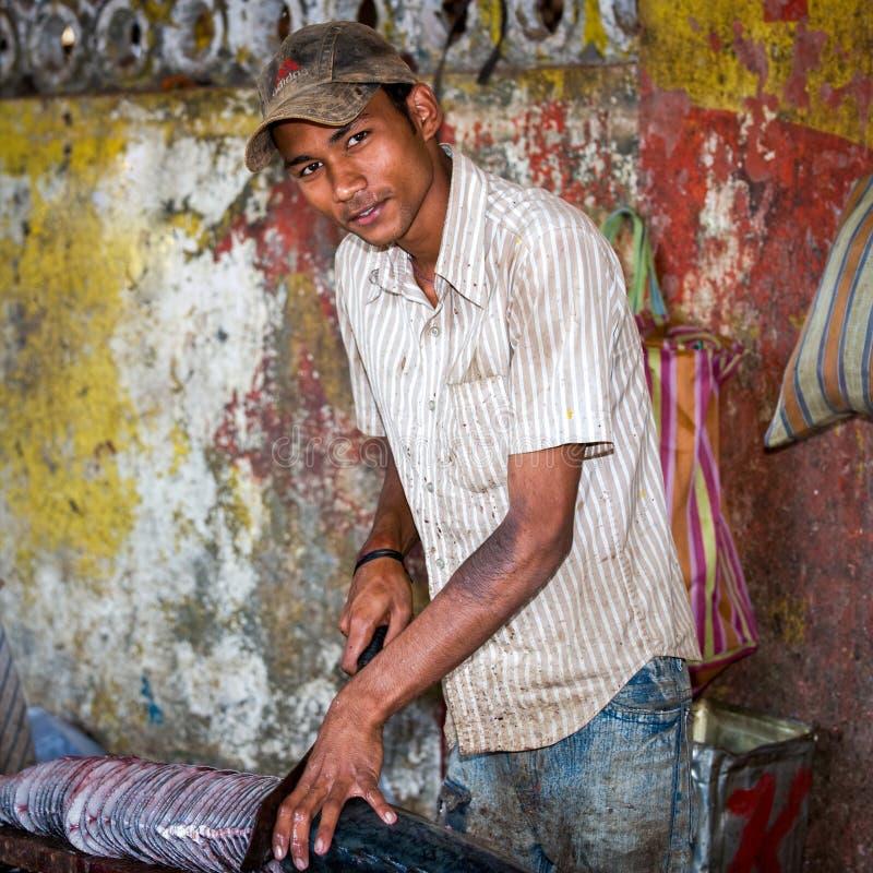 Goa Indien - Februari 2008 - ung man som skivar en stor ny fisk på den berömda veckoMapusa marknaden royaltyfri bild