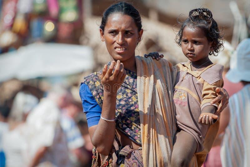 Goa Indien - Januari 2008 - kvinnlig tiggare med ett barn på en berömd veckoloppmarknad i Anjuna arkivfoton