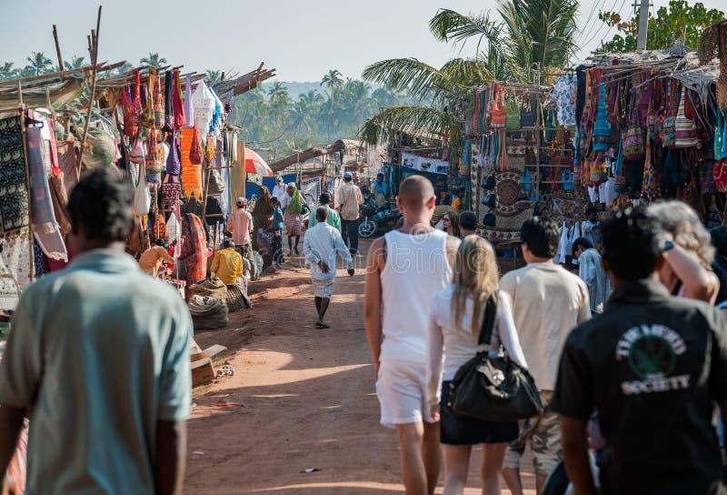 Goa, Indien - Januari 2008 - turister och lokala affärsmän på den berömda veckoloppmarknaden i Anjuna arkivbilder