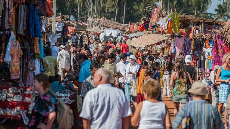 Goa, Indien - Januari 2008 - turister och lokala affärsmän på den berömda veckoloppmarknaden i Anjuna royaltyfria foton