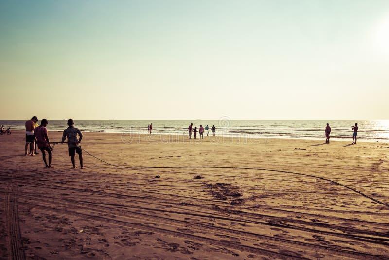 Goa, la India - 20 de diciembre de 2018: Pescadores que pescan con las redes en la playa de Morjim imagen de archivo