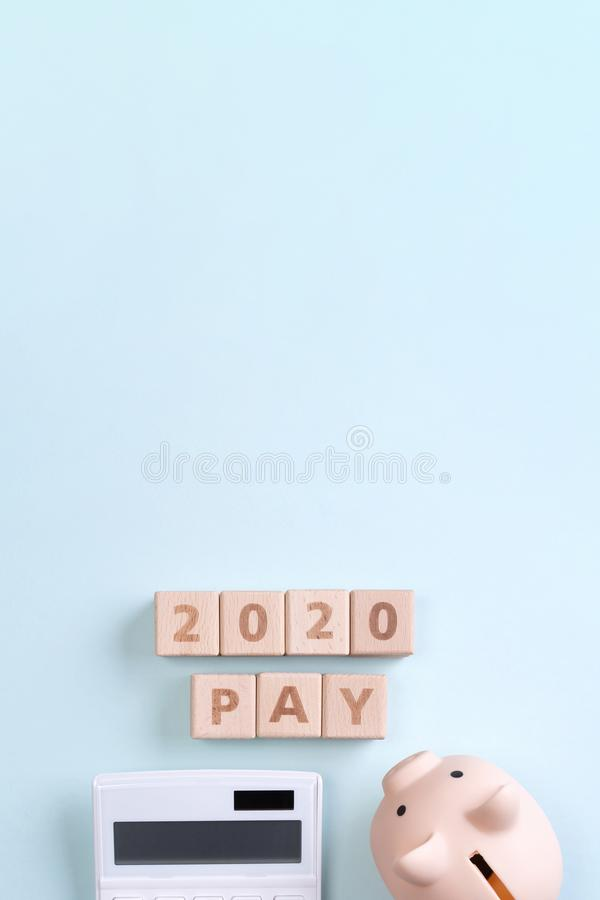2020 goal, finance plan abstract design concept, wood blocks on blue table background with piggy bank and calculator, top view, stock photo