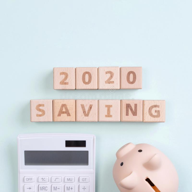 2020 goal, finance plan abstract design concept, wood blocks on green table background with piggy bank and calculator, top view, royalty free stock image