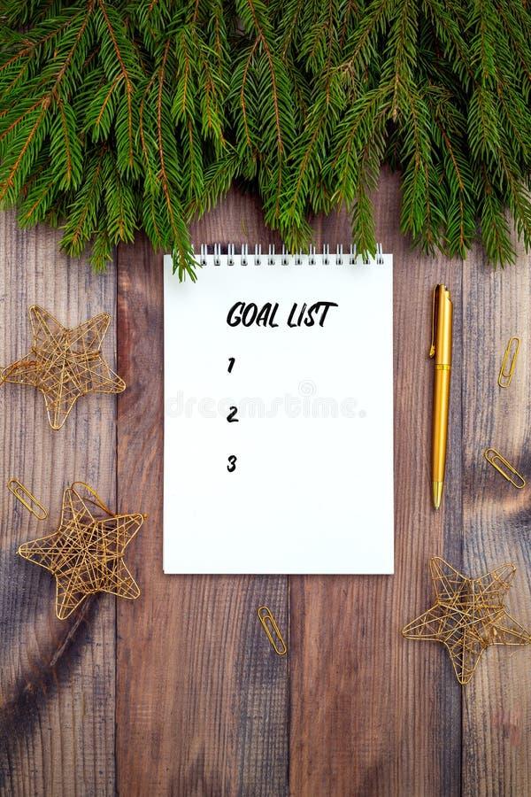 Goal list Notepad en gouden stationair op houten achtergrond kerstaccessoires royalty-vrije stock afbeelding