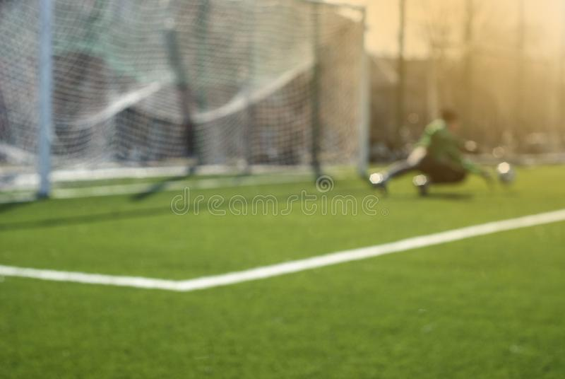 Blurred football background: goalkeeper catches the ball during game moment stock photography