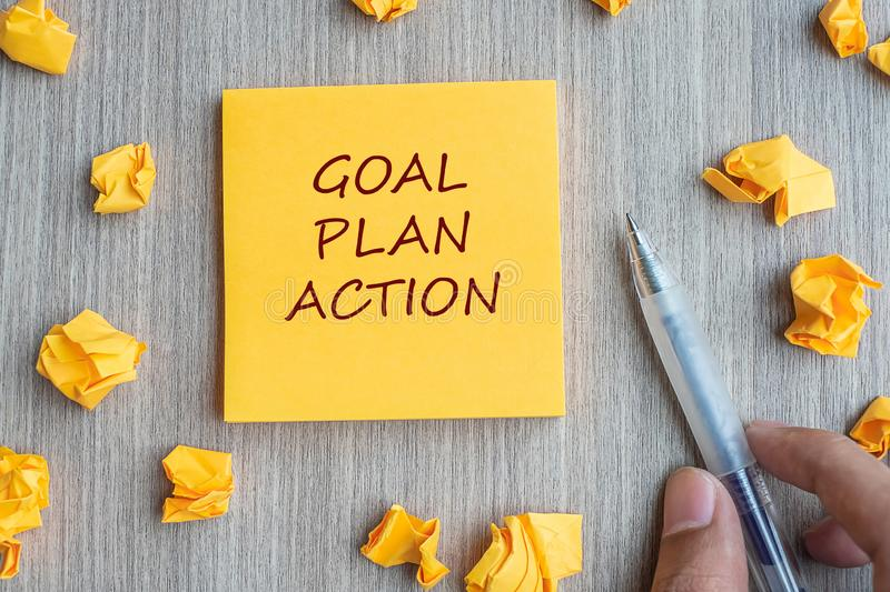 Goal, Plan, Action word on yellow note with Businessman holding pen and crumbled paper on wooden table background. Business Vision stock images
