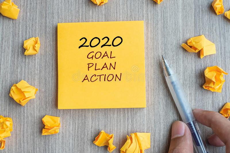 2020 Goal, Plan, Action word on yellow note with Businessman holding pen and crumbled paper on wooden table background. New Year. New Start, Resolutions royalty free stock photography