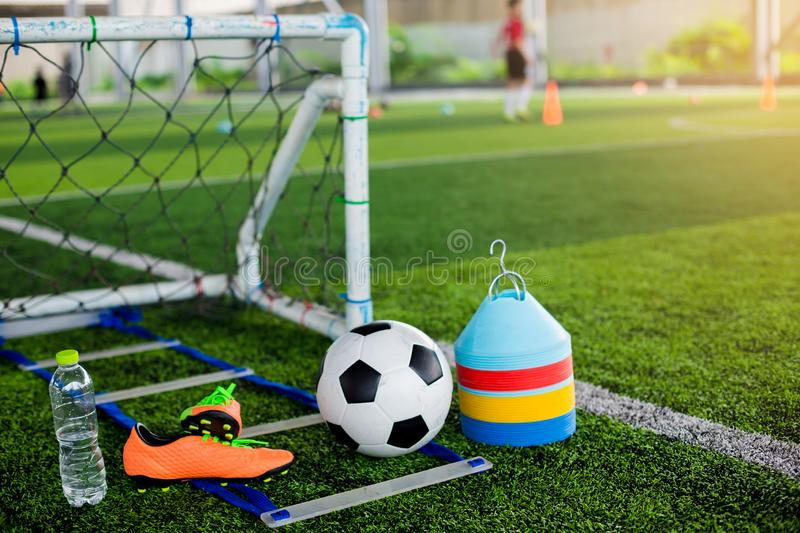 Goal, soccer ball, marker cones, sports shoes and bottle water on green artificial turf. For soccer training equipment stock image