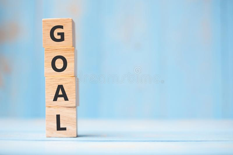 GOAL wooden cubes on blue table background with copy space for text. Business, Mission, Core Value and Solution concept royalty free stock photo