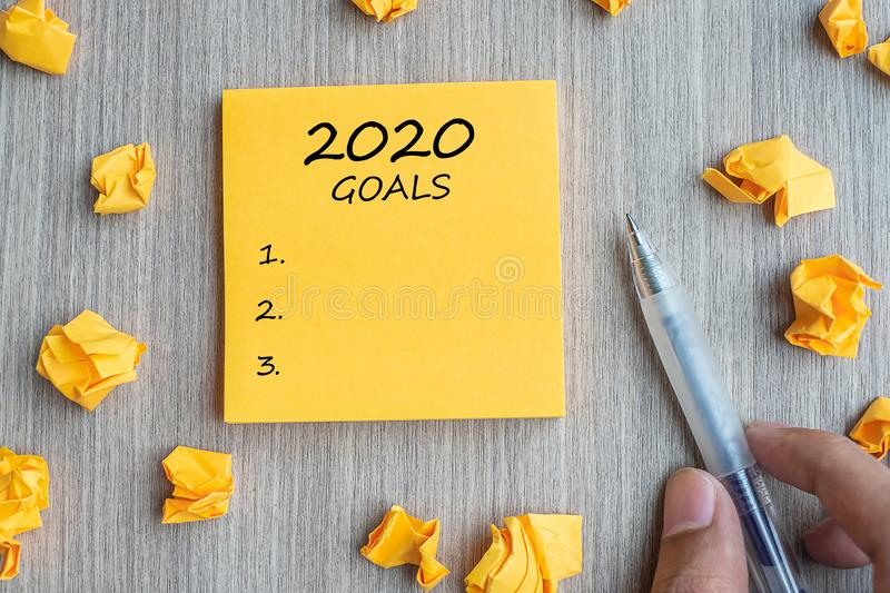 2020 Goal word on yellow note with Businessman holding pen and crumbled paper on wooden table background. New Year New Start, royalty free stock image