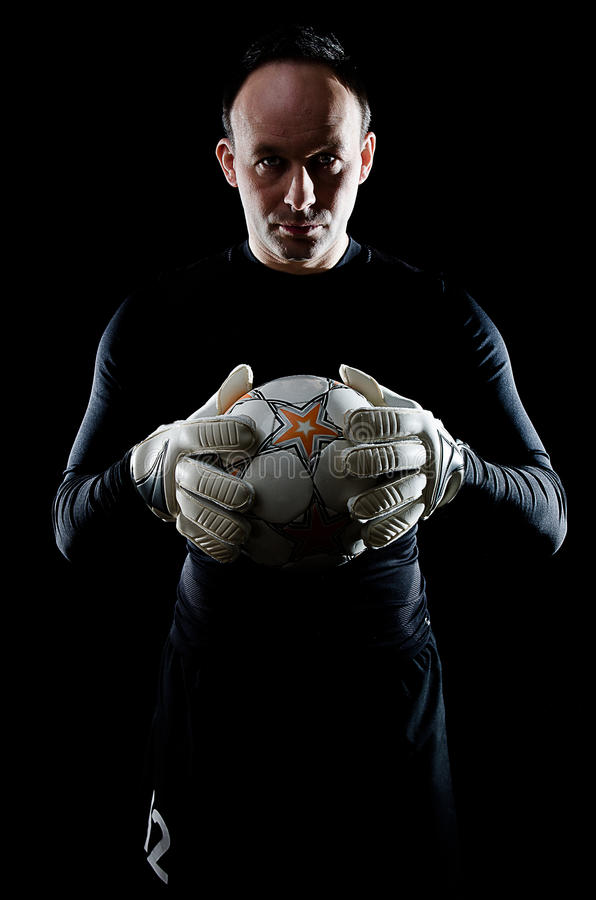 Goalie on black. Portrait of football goalkeeper on black background. Man is wearing goalie gloves and goalkeeper's blouse. Studio shot royalty free stock photo