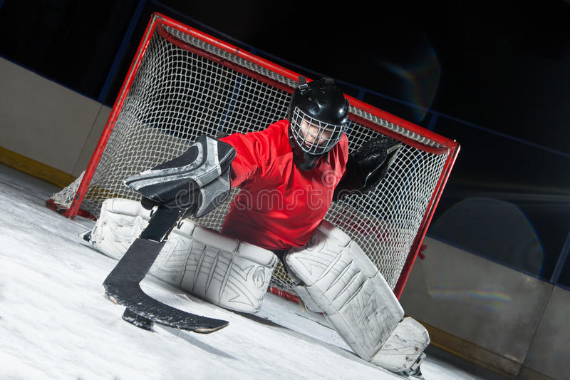 Goalie blocking a puck with stick. Hockey goalie blocking a puck with stick royalty free stock photography