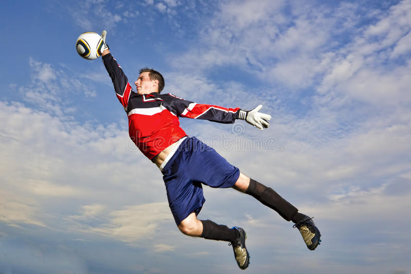 Goalie jumps to catch soccer ball. A goalie jumps into the air against a blue sky with clouds to catch a soccer ball royalty free stock image
